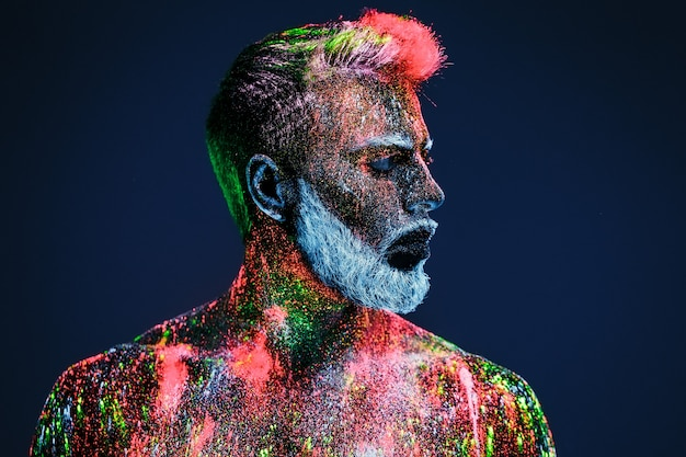 概念。理髪店のひげを生やした男。理髪店でスタイリッシュなひげを生やした男がトリミングされます。男は紫外線の粉で飾られています。
