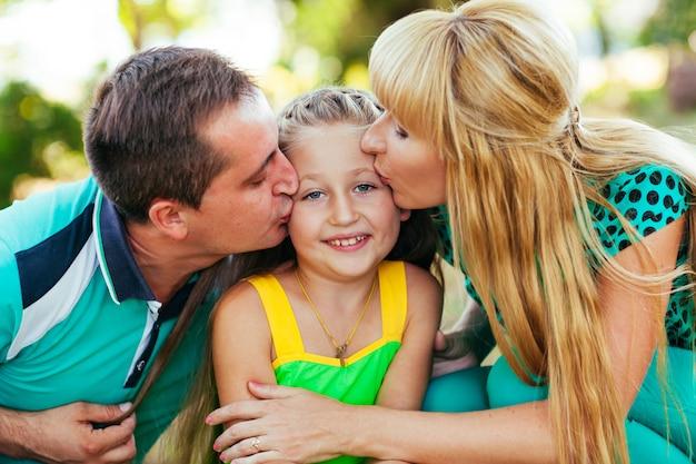 公園で若くて美しい家族。母、父と娘