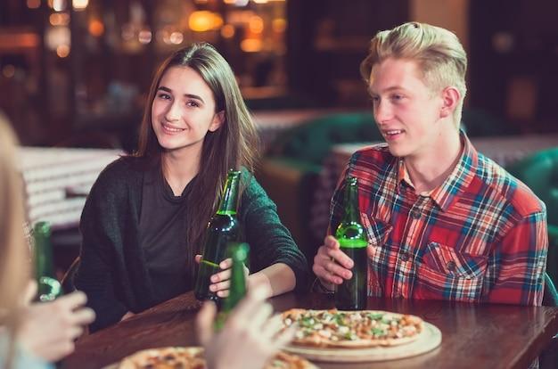 Друзья пьют и едят пиццу в баре