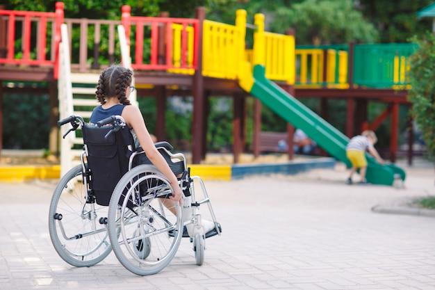 骨折した足を持つ少女は、遊び場の前で車椅子に座っています。