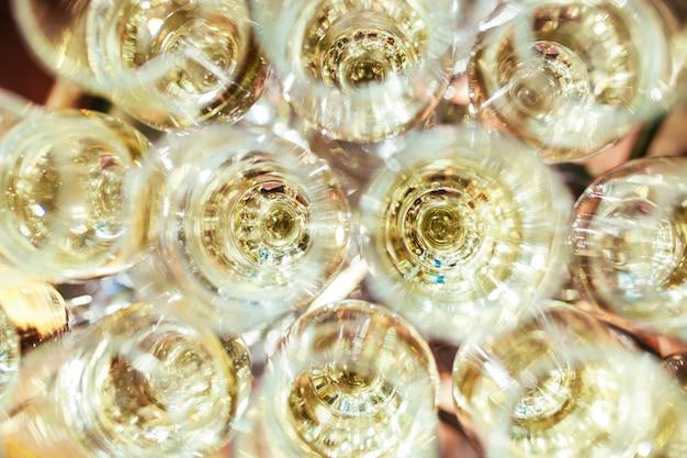 パーティーやお祝い中にサービングテーブルの上に行にシャンパン立ってエレガントなメガネ