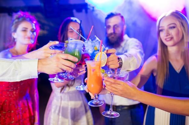 カクテルと友達はパーティーで飲みます。