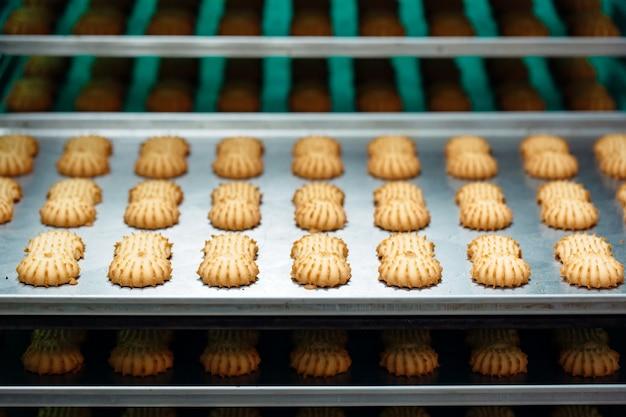 Песочное. производство песочного печенья на кондитерской фабрике. песочное печенье на металлической стойке после выпечки в духовке.