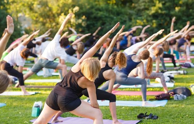 Большая группа взрослых, посещающих занятия йогой на улице в парке