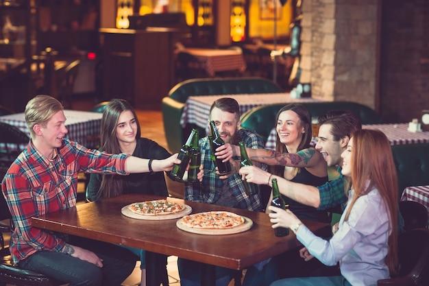 Друзья пьют в баре, они сидят за деревянным столом с пивом и пиццей.