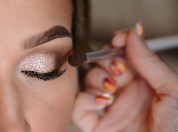 Портрет красивой гламурной женщины с темными вьющимися волосами, визажист заканчивает макияж невесте на свадебное утро