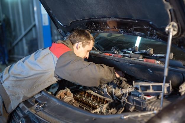 Автомеханик работает в гараже. услуги по ремонту.