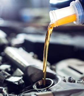 Моторное масло льется на двигатель автомобиля.