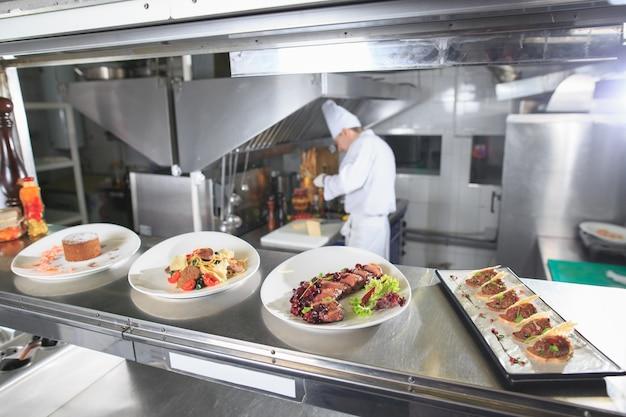 Распределительный стол на кухне ресторана. шеф-повар готовит еду на фоне готовых блюд.