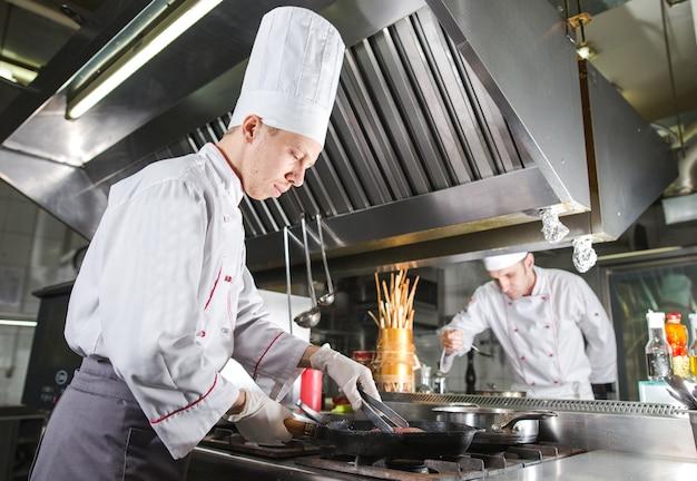 Шеф-повар в кухне ресторана на плите с кастрюлей, приготовление пищи