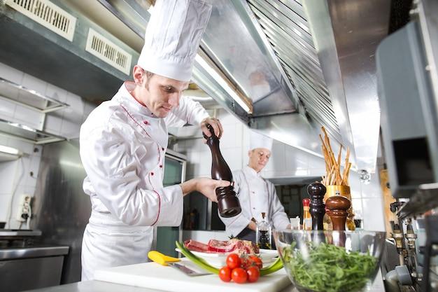 Шеф-повар готовит блюдо на кухне от ресторана.