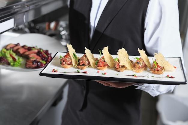 Официант с готовыми блюдами на кухне ресторана.