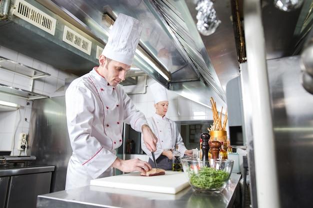 まな板でシェフの肉を切る、プロの料理人がナイフを保持し、レストランで肉を切る