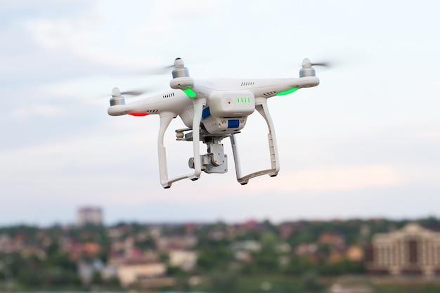 Беспилотный четырехъядерный вертолет с цифровой камерой высокого разрешения, летающий над городом