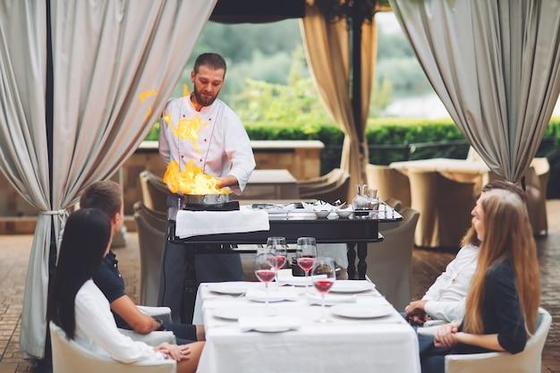 Шеф-повар готовит фуа-гра перед гостями.
