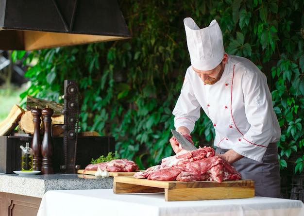 男料理人がレストランでナイフで肉を切る。