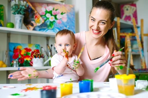 お母さんと娘は絵を描く学校のキャンバスに絵を描きます。