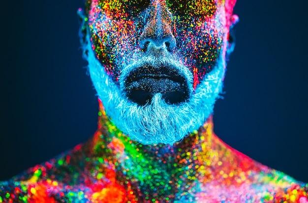 概念。ひげを生やした男の肖像。男は紫外線の粉で塗られています。