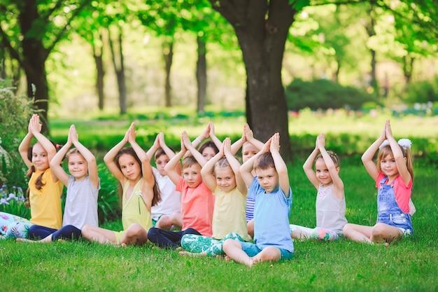 Большая группа детей занимается йогой в парке, сидя на траве.