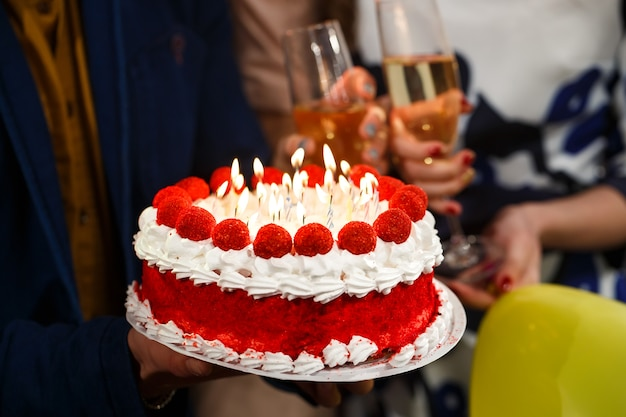 お誕生日おめでとうございます!グループの人がケーキを持っています。