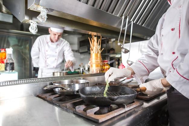 パン、料理とストーブのレストランのキッチンでシェフ