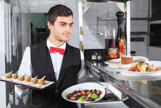 レストランのキッチンで準備ができた料理とウェイター。