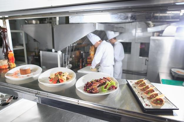 レストランのキッチンの配布テーブル。シェフは完成した料理の背景で食事を準備します。