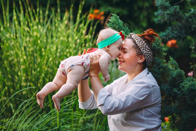幸せな調和のとれた家族の屋外。母は赤ちゃんを投げ、笑って、夏に遊んで