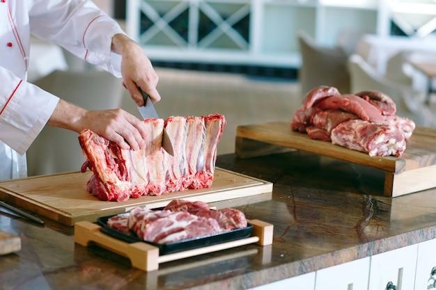 Мужчина-повар режет мясо ножом в ресторане.