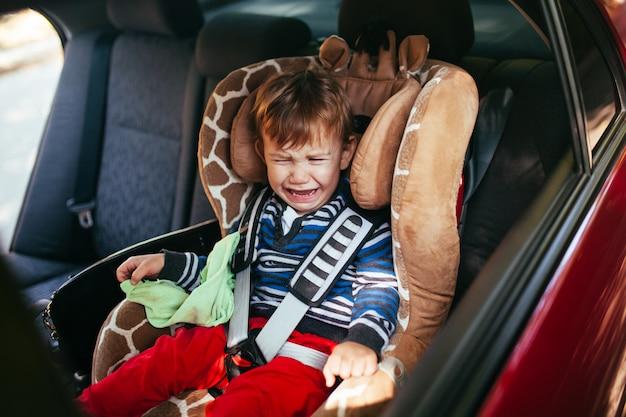 安全車の座席で泣いている男の子