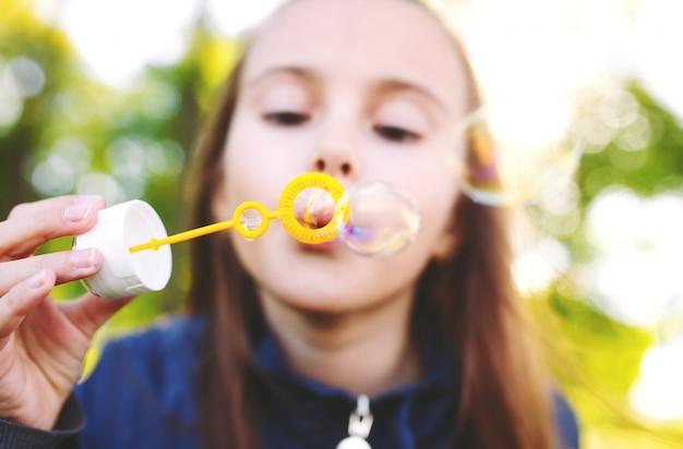 女の子はシャボン玉で遊ぶ。