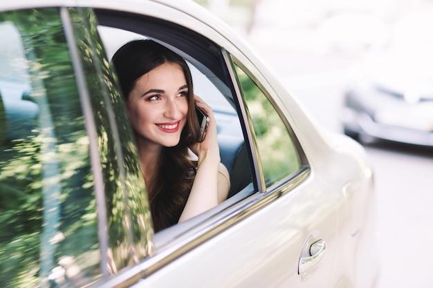 若い女の子が車の後部座席に座って電話で話しています。