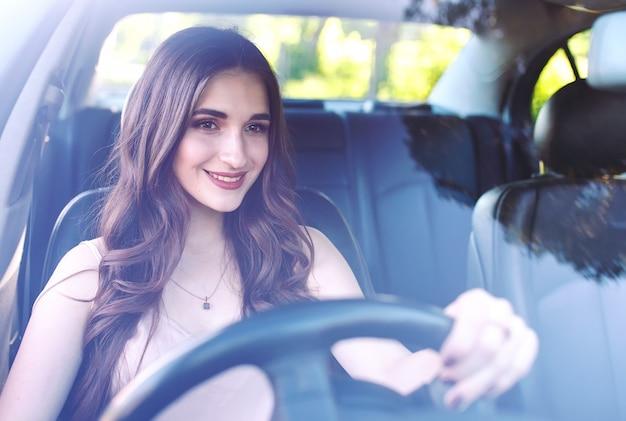 Молодая девушка за рулем автомобиля.