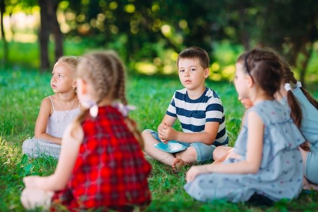 子供と教育、公園で男の子と女の子に本を読んで教育者としての仕事で若い女性