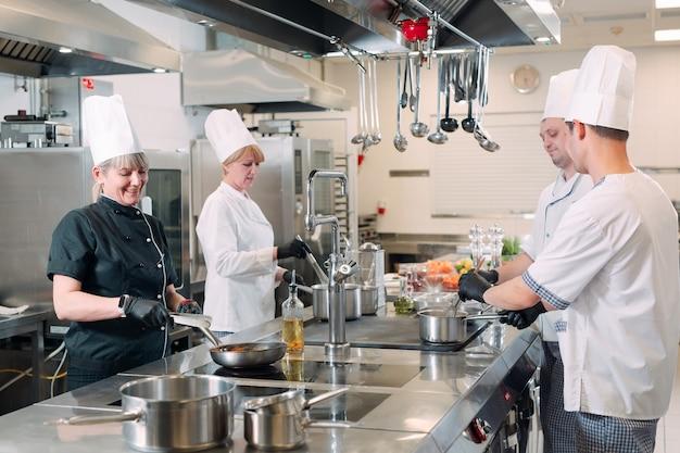 料理人はレストランのプロのキッチンで電気ストーブで食事を準備します