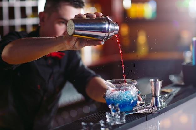 おしゃれなグラスに新鮮なカクテルを注ぐバーテンダー