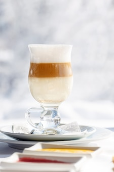Кофе латте на террасе перед рестораном на фоне снега