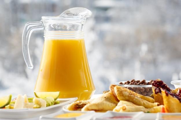 Зимний завтрак апельсиновый сок и блины на террасе перед рестораном на фоне снега