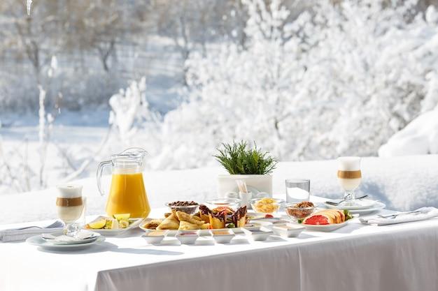 雪を背景にレストランの外のテラスで冬のパンケーキ朝食パンケーキ、フルーツ、ジュース、コーヒー