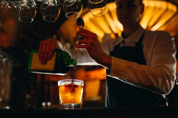 バーテンダーはバーでカクテルを準備しますバーテンダーはボトルからアルコールを注ぎます