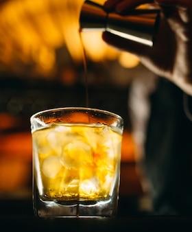 バーテンダーがバーにウイスキーを注ぐ