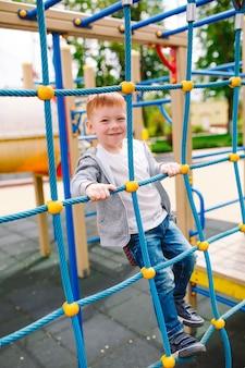 小さな男の子が遊び場で遊んでいます。