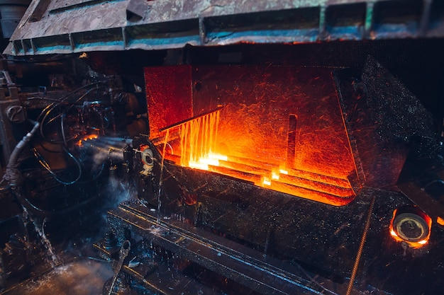 Горячая сталь на конвейере в сталелитейном заводе