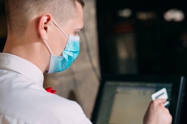 Малый бизнес, люди и концепция обслуживания. человек или официант в медицинской маске на прилавке с кассы, работающие в баре или кафе.