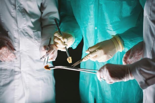 医療機器を保持している外科医の手のクローズアップ。外科医が手術を行います。