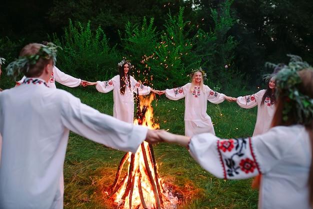 В середине лета. молодежь в славянском кружке одежды танцует у костра в лесу.