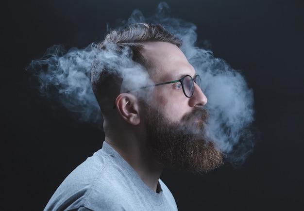 概念。煙が頭の男を包んでいた。煙でひげを生やした、スタイリッシュな男の肖像画。間接喫煙。