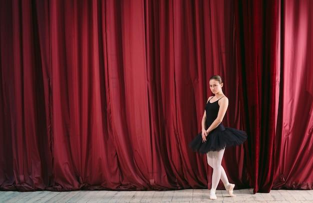 黒のドレスを着た若いバレリーナが舞台裏で電車に乗っています。