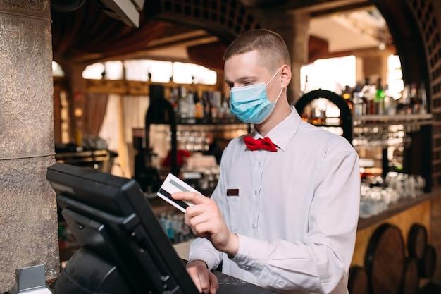 中小企業、人々、サービスのコンセプト。男またはバーまたはコーヒーショップで働くキャッシュボックスとカウンターで医療マスクのウェイター。