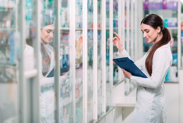 タブレットで薬局ドラッグストアで働く薬剤師の化学者女性。